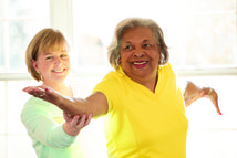 Woman assisting senior woman exercise