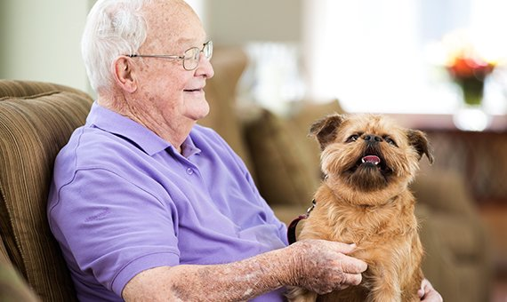 Senior man sitting with a dog on his lap.