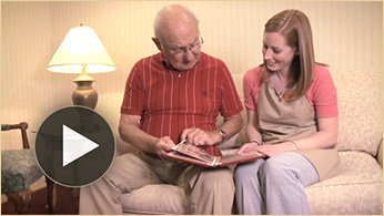Man and woman reading with play button in foreground